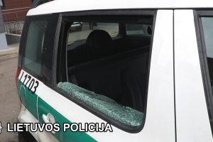 Girta mergina išspyrė policijos automobilio stiklą